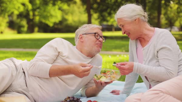 Senior couple eating salad at picnic in park Royalty-free stock video