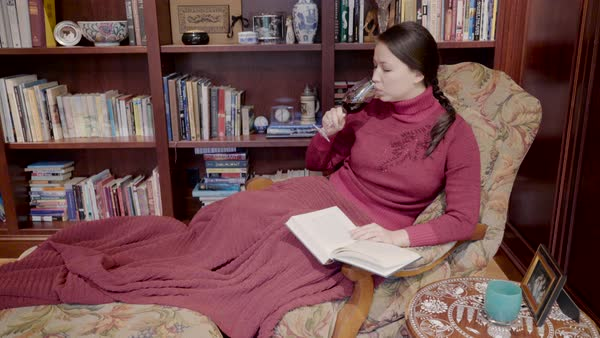 Medium shot of a woman reading in an armchair Royalty-free stock video
