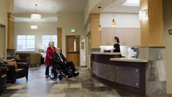 Steadicam shot of a senior couple arriving to a reception desk Royalty-free stock video