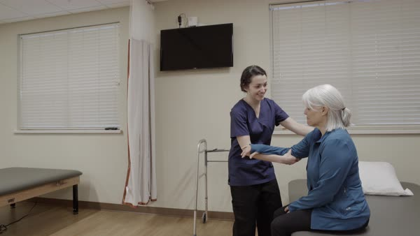 Panning shot of a physiotherapist lifting an arm of a senior woman Royalty-free stock video