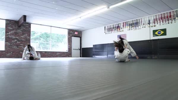 Instructor tying a belt of a boy in a dojo - Stock Video