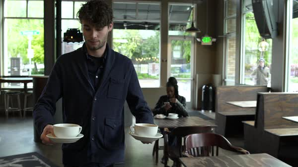 Young man bringing coffee to a young woman in a coffee shop Royalty-free stock video