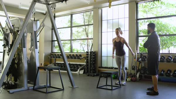 Young woman box jumping with a coach in a gym Royalty-free stock video
