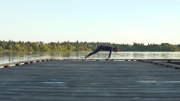 A young woman doing yoga on a dock Royalty-free stock video