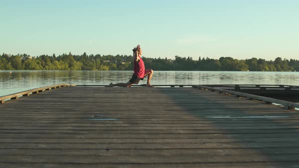 A young man doing yoga on a dock Royalty-free stock video