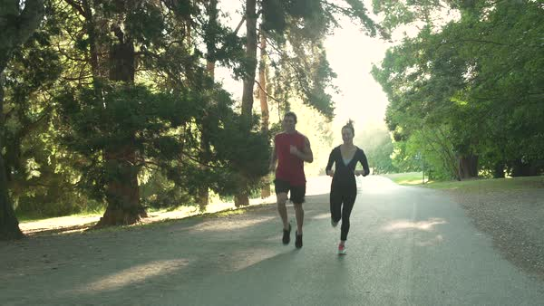 Two young people running in a forest Royalty-free stock video