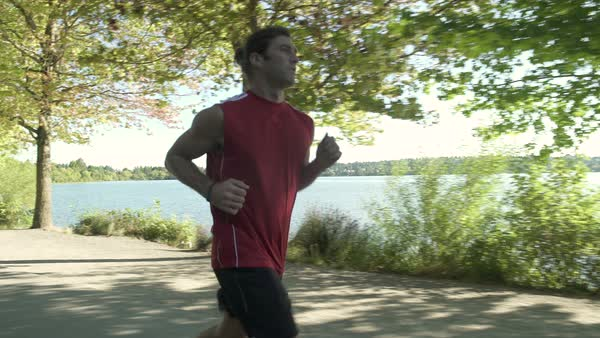 A young man running by a lake Royalty-free stock video