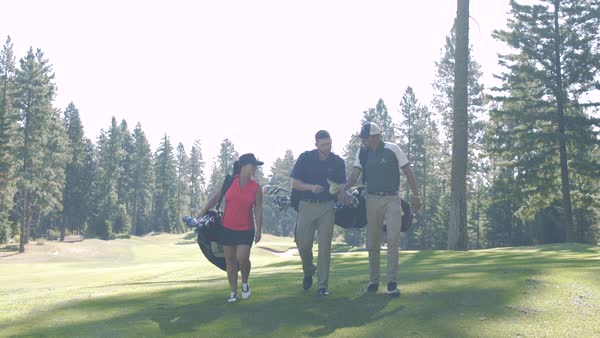 Three people walking on a golf course carrying golf bags Royalty-free stock video