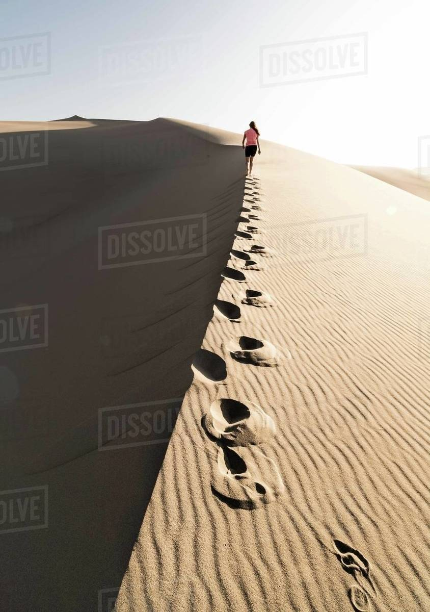 Rear view of a woman walking on sand dune in desert, Death Valley, California, United States of America Royalty-free stock photo