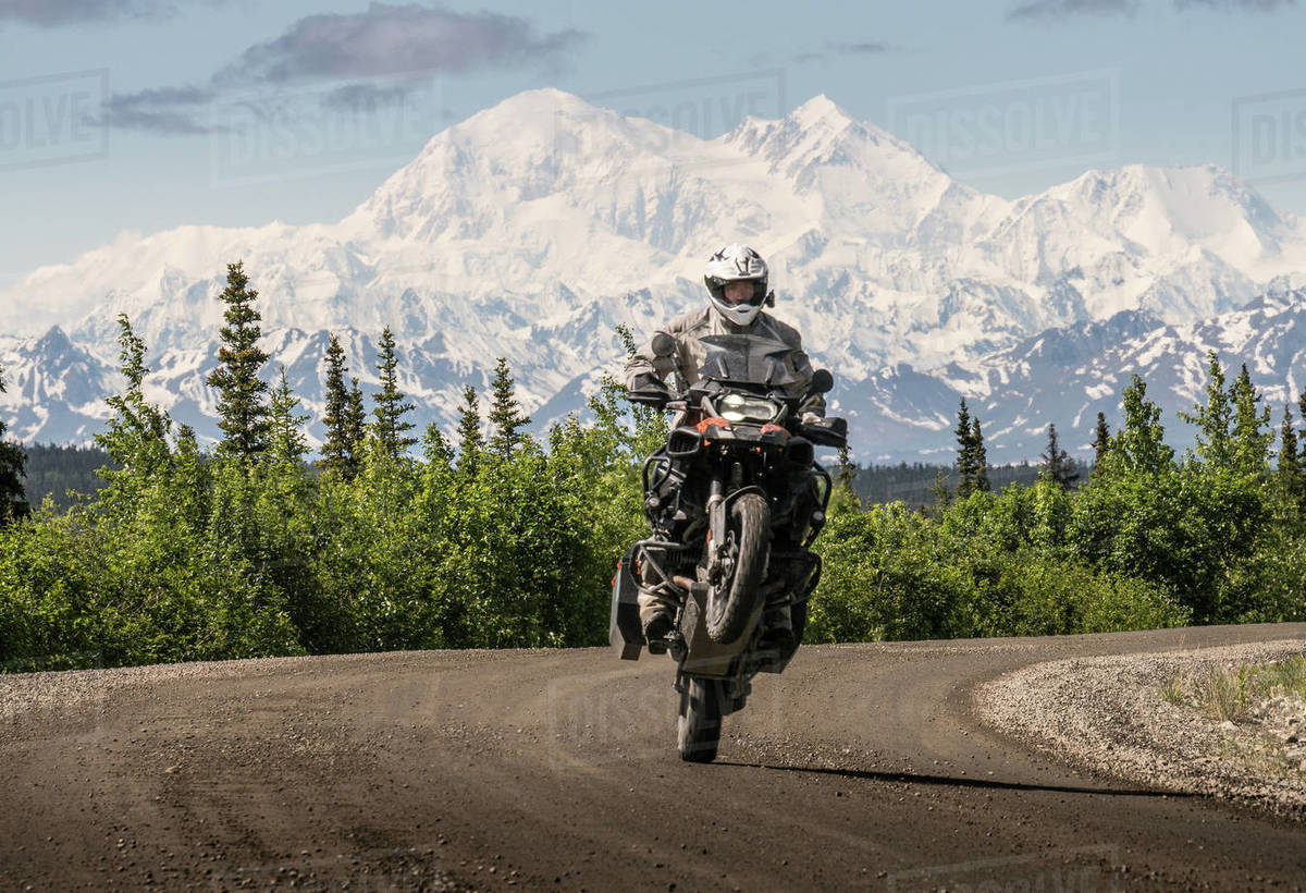Biker riding motorbike on road against snowcapped mountains Royalty-free stock photo