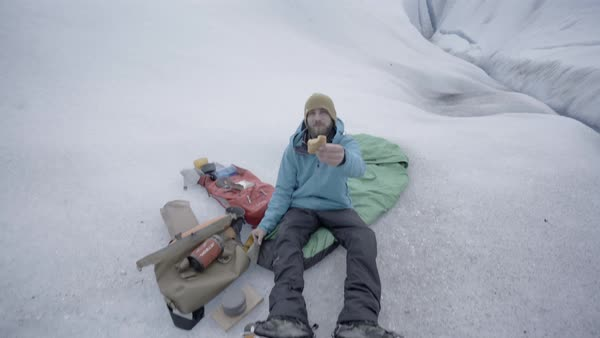 Point of view shot of a man eating while sitting on a sleeping bag Royalty-free stock video