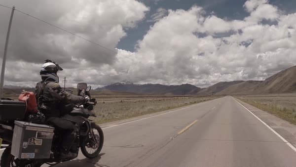 Tracking shot of a loaded up motorcycle driving on a road Royalty-free stock video