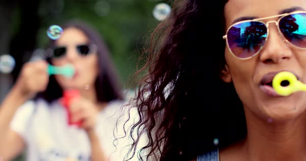 Two happy trendy young women celebrating and having fun blowing soap bubbles with focus to a pretty young woman in modern sunglasses in the foreground Royalty-free stock video