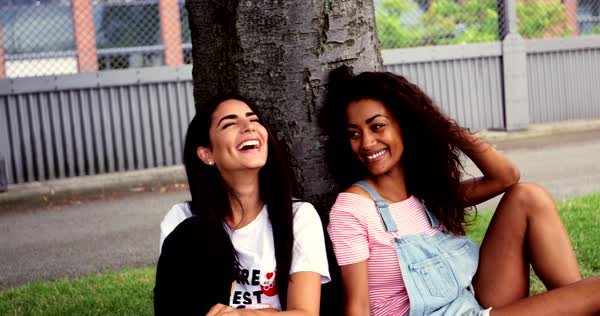 Pair of beautiful young adult women sitting next to each other under tree near urban apartment building outdoors Royalty-free stock video