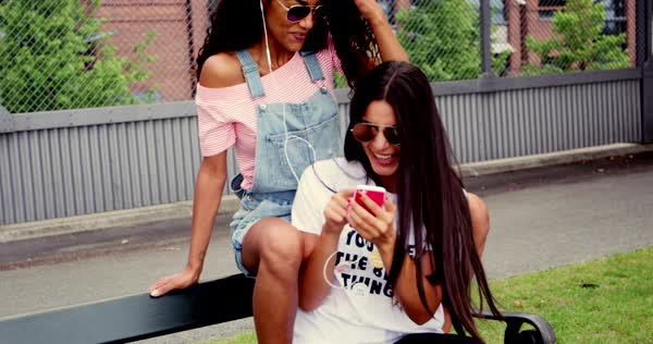 Two trendy young girlfriends wearing casual clothes and sunglasses relaxing in an urban park smiling happily as they read a text message on a mobile phone Royalty-free stock video