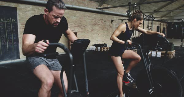 Fit man and woman exercising in gym, working out on cardio bike Royalty-free stock video