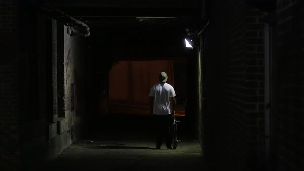 Hand-held shot of a man standing in a tunnel with a skateboard Royalty-free stock video