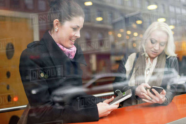 Sweden, Young women using mobile phones at cafe Royalty-free stock photo