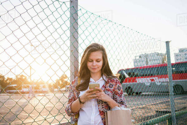 Israel, Tel Aviv, Young woman standing by chain-link fence and using smart phone Royalty-free stock photo