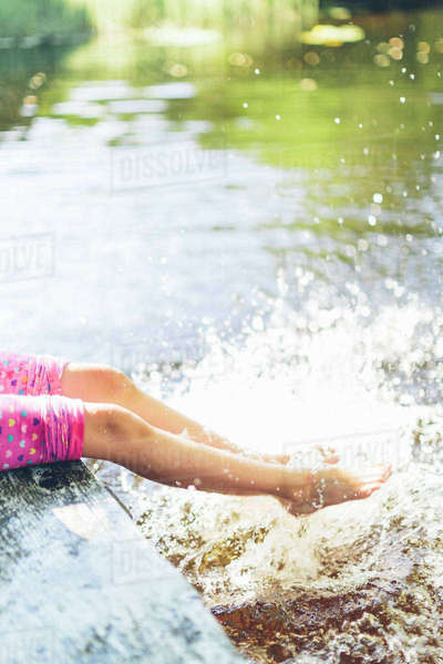 Sweden, Low section of girl (8-9) splashing water with legs Royalty-free stock photo