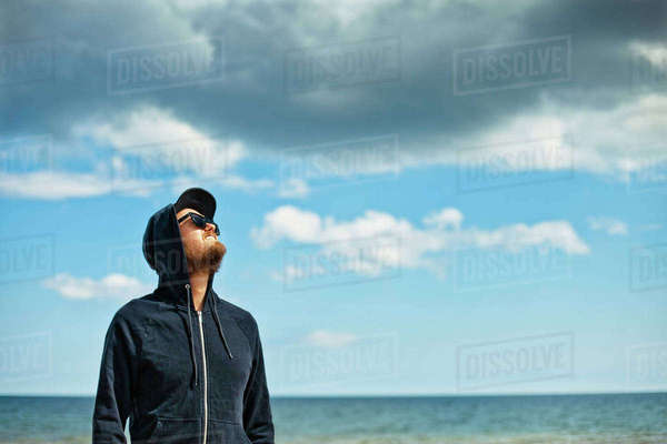 Sweden, Oland, Portrait of man in hooded shirt looking at sky Royalty-free stock photo