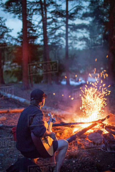 Sweden, Medelpad, Man playing guitar by campfire Royalty-free stock photo