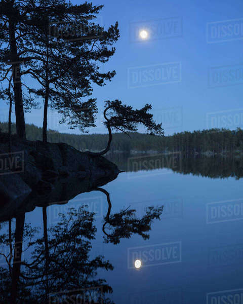 Sweden, Vastergotland, Tiveden National Park, Stora Trehorningen, Lake with forest under blue sky with moon Royalty-free stock photo
