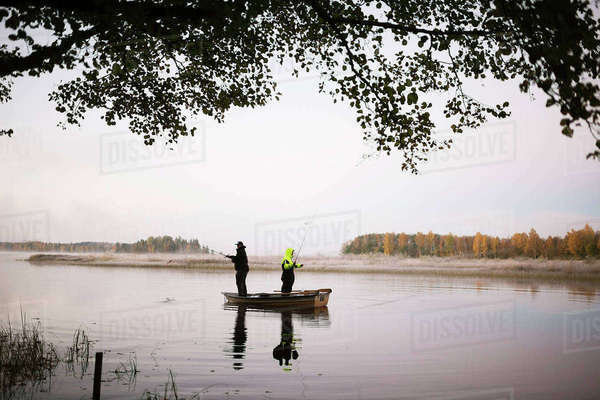 Sweden, Vastmanland, Bergslagen, Torrvarpen, Young men fishing in lake at sunset Royalty-free stock photo