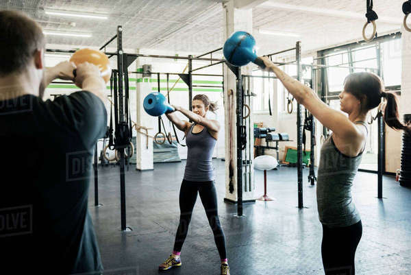 Germany, Young women and man swinging kettlebells in gym Royalty-free stock photo