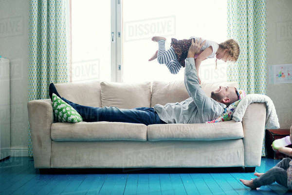 Finland, Father playing with daughters (12-17 months, 2-3) in living room Royalty-free stock photo