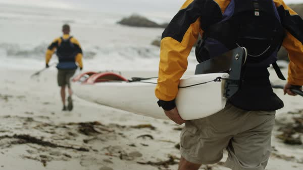 Two men carrying kayak to the ocean in slow motion Royalty-free stock video