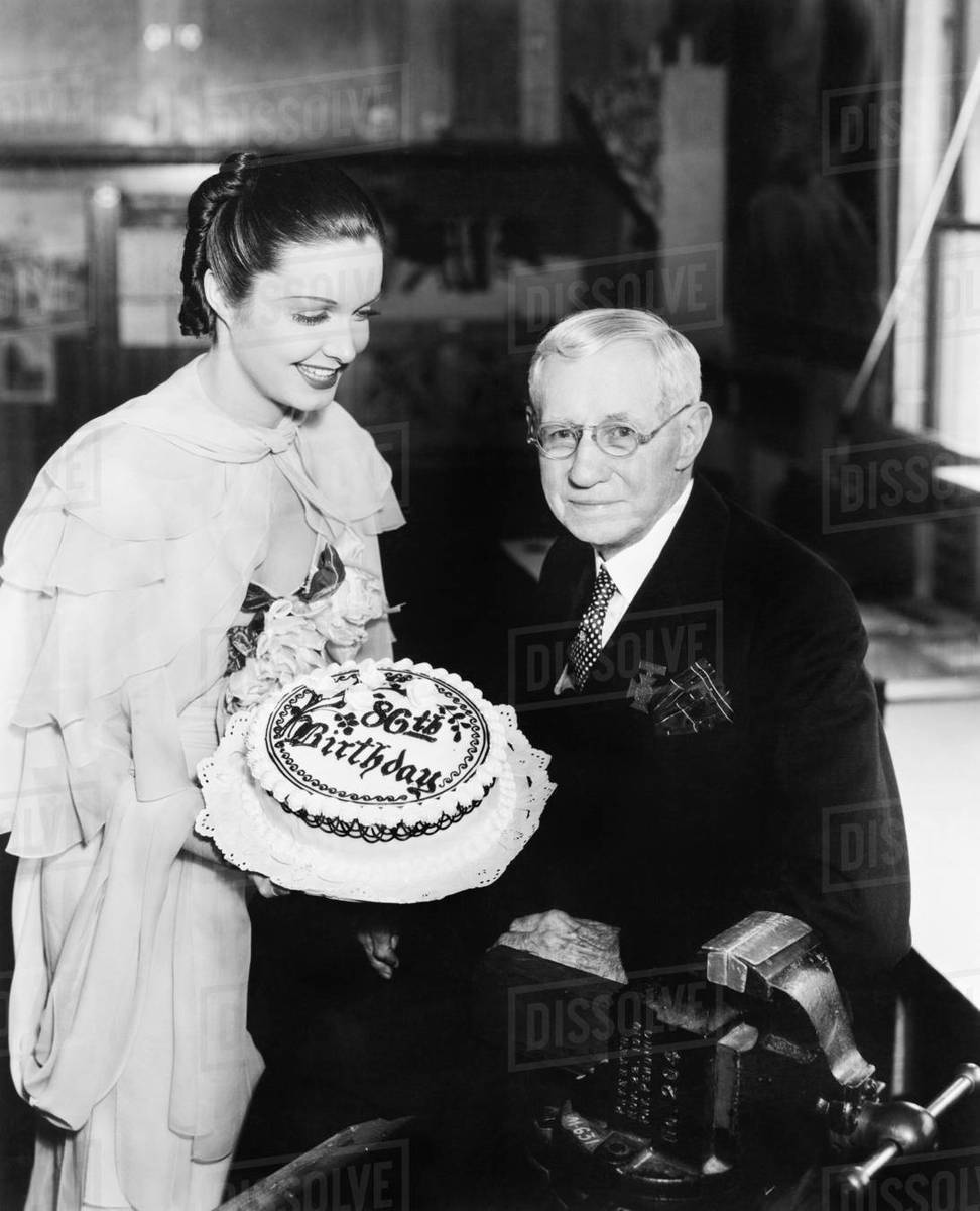 Young Woman Presenting A Birthday Cake To An Elderly Man