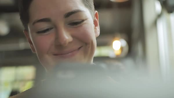 Slow motion shot of a genderqueer person using a smartphone in a cafe Royalty-free stock video