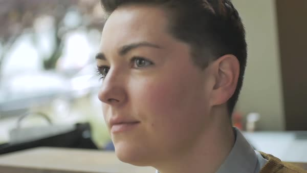 Slow motion shot of a genderqueer person sitting in a cafe and looking away Royalty-free stock video