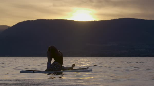 A young woman doing yoga on a paddleboard in Okanagan Lake with mountain range in background Royalty-free stock video