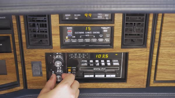 Hand-held shot of a person setting a radio station in an old-fashioned car Royalty-free stock video