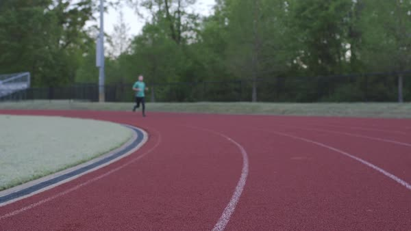 Dolly shot of a man running on an outdoor track Royalty-free stock video