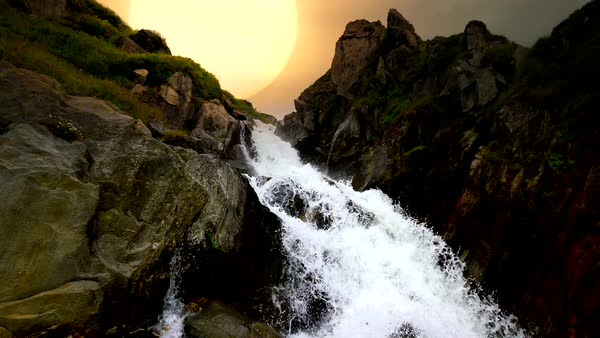Waterfall in rocky landscape in the mountains with beautiful sunset background in Switzerland Royalty-free stock video