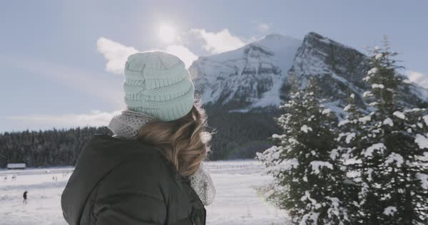 Slow motion shot of a woman walking alone on a snowy road on a beautiful winter day in the mountains Royalty-free stock video