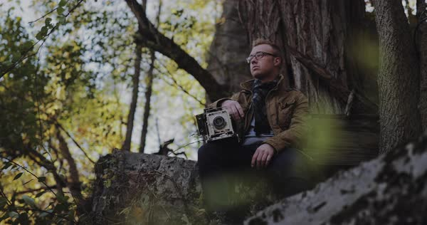 Hand-held shot of a photographer sitting on a rock in a forest Royalty-free stock video