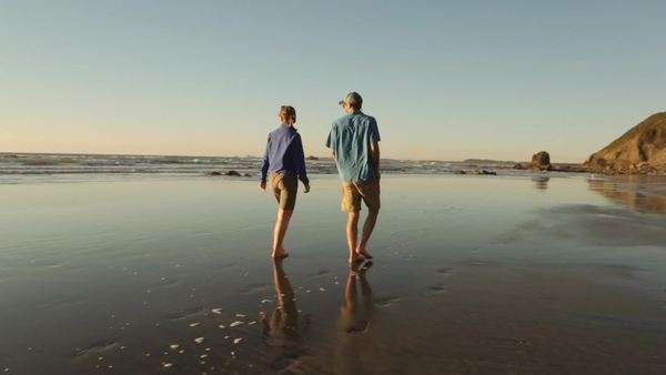 Wide shot of couple walking along a beach Royalty-free stock video
