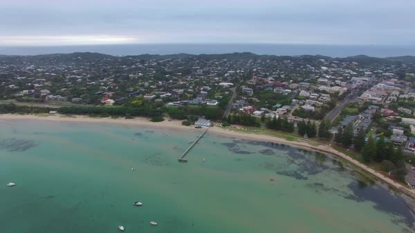 Forward flight over bay waters towards Sorrento Long pier and the coastline suburb at dawn. Mornington Peninsula, Victoria, Australia Royalty-free stock video