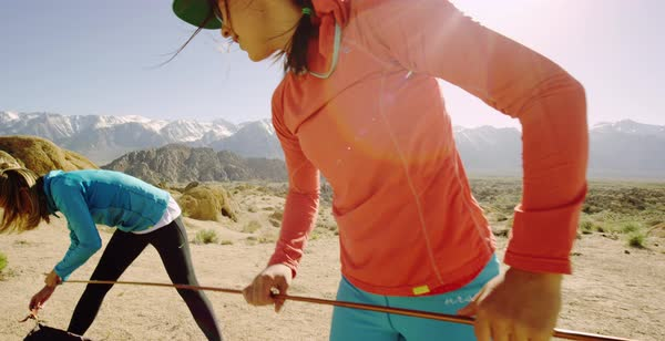 Hand-held shot of two women setting up tent poles Royalty-free stock video
