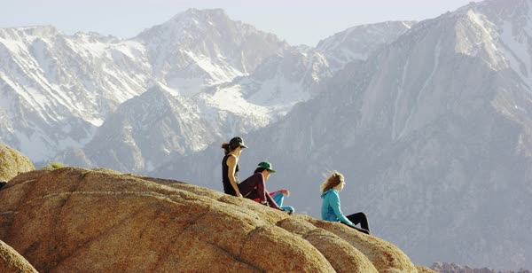 Panning shot of three female hikers enjoying view of mountains Royalty-free stock video