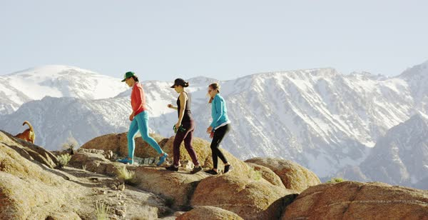 Tracking shot of three women hiking in Alabama Hills with a dog Royalty-free stock video
