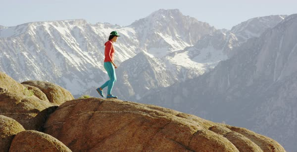 Tracking shot of a female hiker walking to a rock to enjoy view of mountains Royalty-free stock video