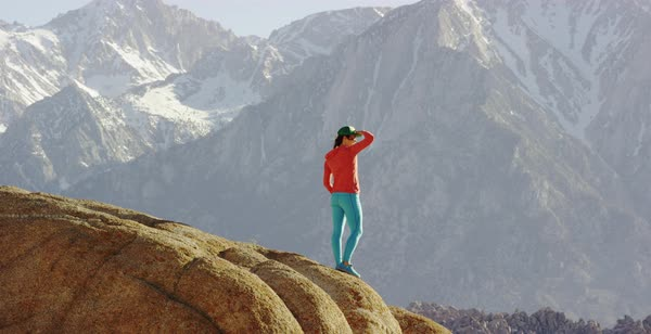 Tracking shot of a female hiker enjoying view of mountains while standing on a rock Royalty-free stock video
