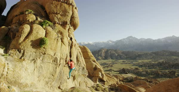 Tilt-up shot of a woman climbing up a rock in Alabama Hills Royalty-free stock video