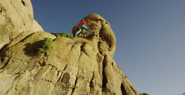 Slow motion shot of a woman climbing up a rock in Alabama Hills Royalty-free stock video