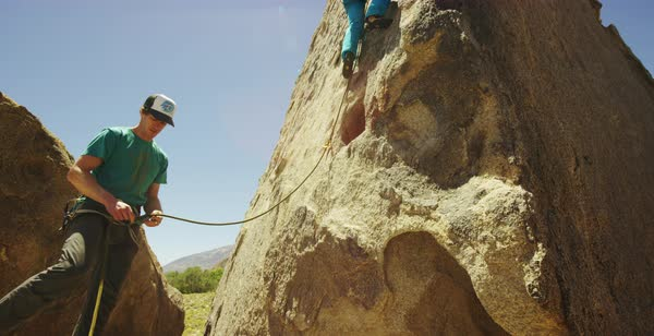 Tilt-up shot of a man holding rope for a rock climbing woman Royalty-free stock video